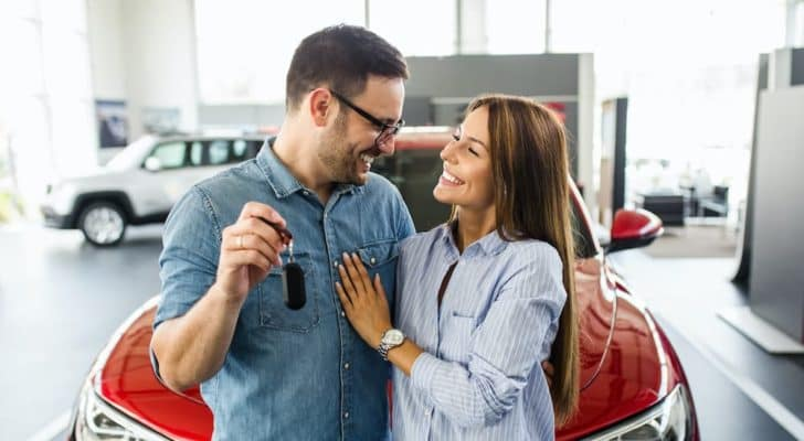 A couple is holding a set of keys after searching for new cars in stock near you.