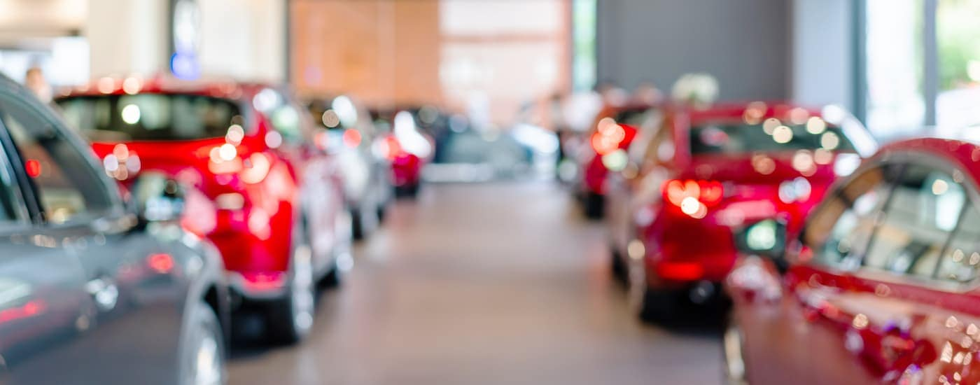 A blurred image shows a car dealership full of cars.