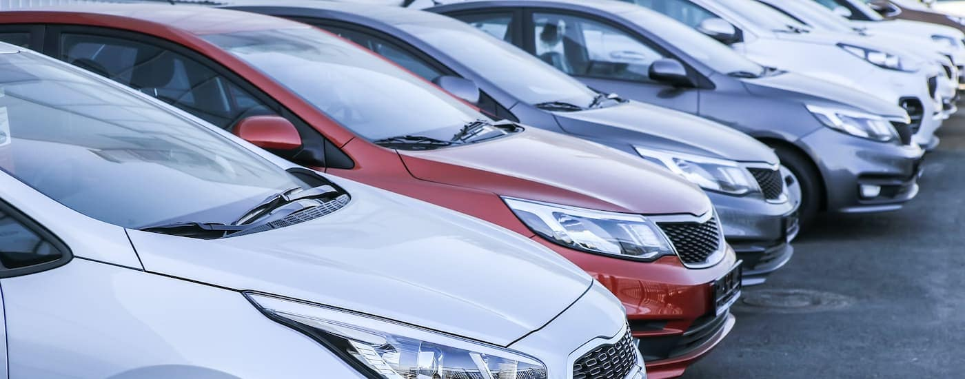 A row of cars is shown at a car dealership.