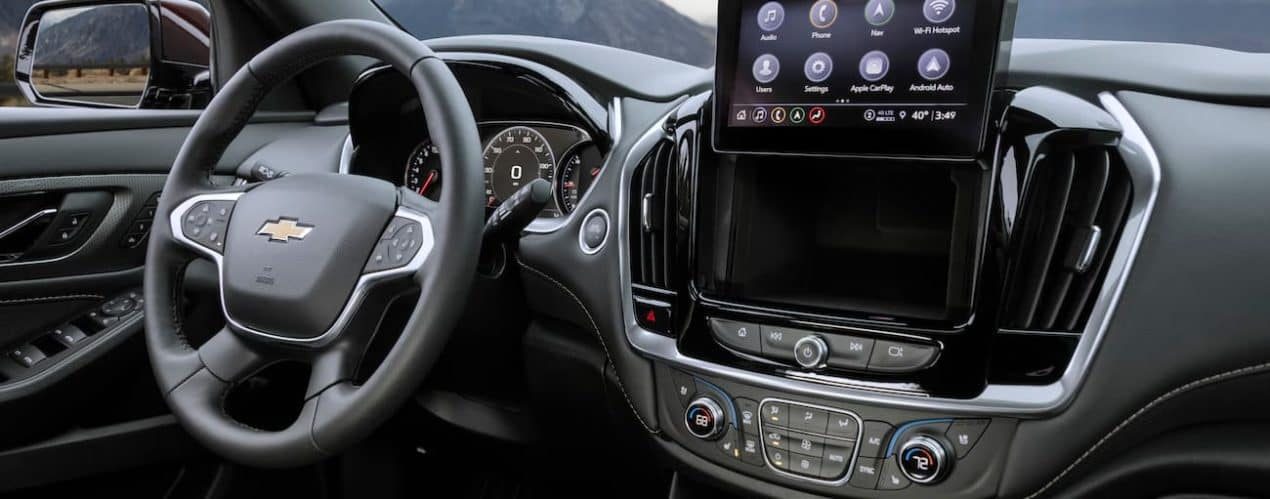 The black interior of a 2022 Chevy Traverse shows the steering wheel and infotainment screen.