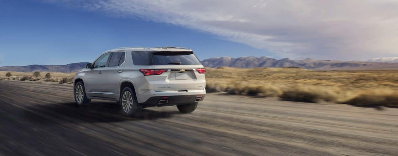 A white 2022 Chevy Traverse is shown from the rear driving on an open highway.