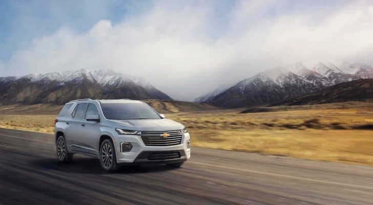 A silver 2022 Chevy Traverse is shown driving on an open highway.