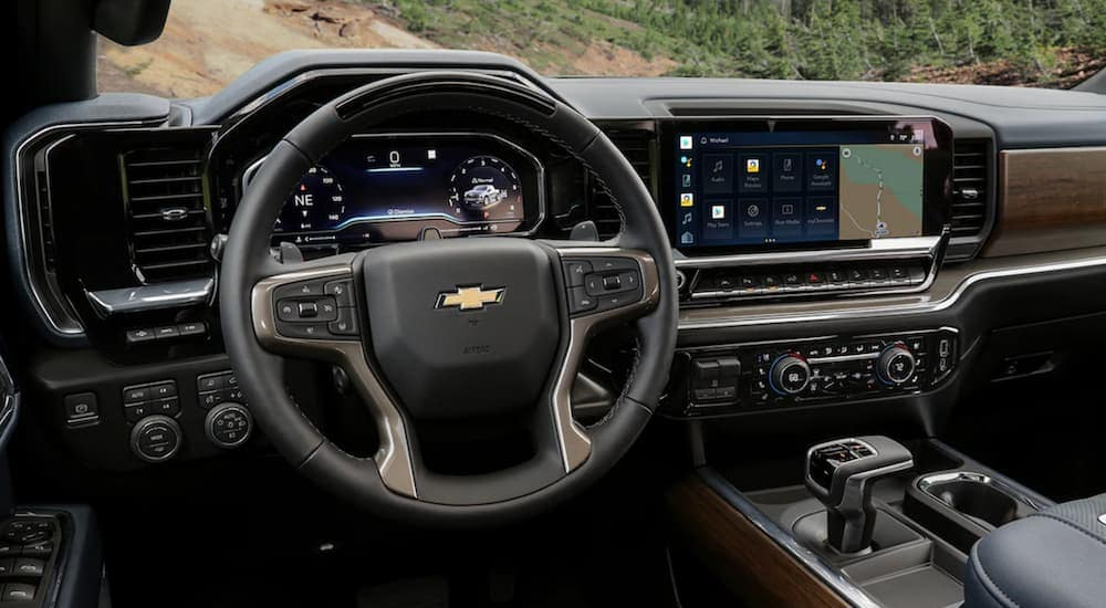 The black interior of a 2022 Chevy Silverado 1500 shows the steering wheel and infotainment screen.