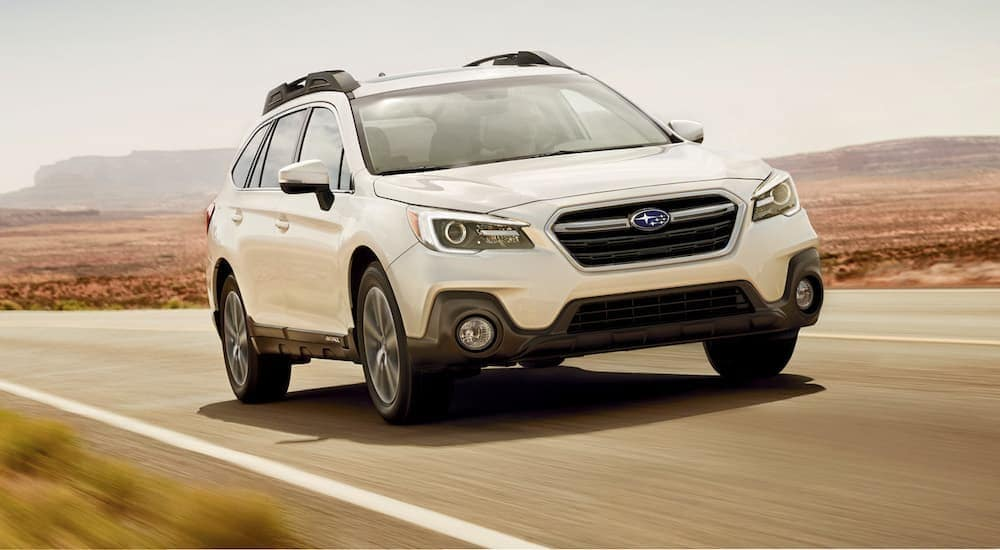 A white 2019 Subaru Outback is shown from the front driving on an open road.