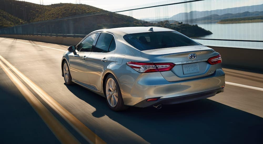 A silver 2020 Toyota Camry XLE Hybrid is shown from the rear driving on an open highway.