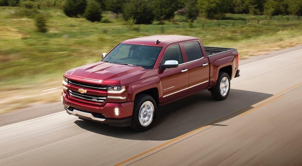 A red 2018 Chevy Silverado 1500 is shown driving on an open road after leaving a used truck dealer in Lexington.