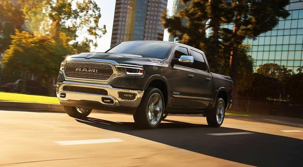 A grey 2019 Ram 1500 is shown from a low angle driving in a city.