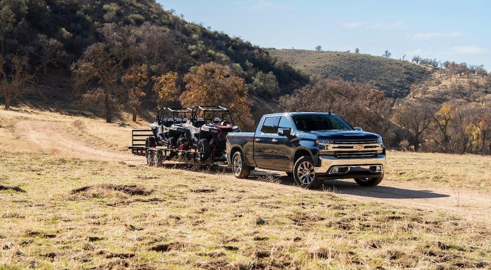 A black 2020 Chevy Silverado 1500 is shown towing two ATVs.