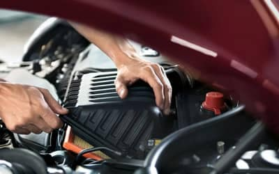 Person working under the hood of a Mini