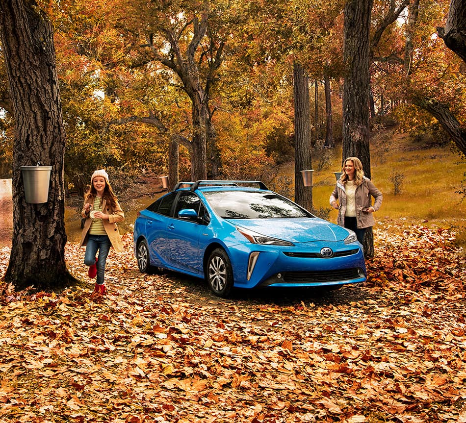 Halterman's Toyota is a Toyota Dealership near Neola, PA | Mother and daughter in autumn woods by 2020 Toyota Prius