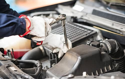 Halterman's Toyota is a Toyota Dealership near Analomink PA | Close up of mechanic hands working under the hood of Toyota vehicle