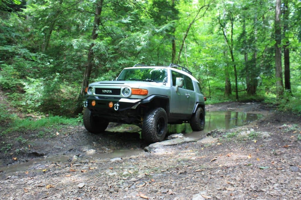 Halterman's Toyota is a Toyota Dealership near Marshalls Creek, PA | 2014 Toyota FJ cruiser driving through the woods