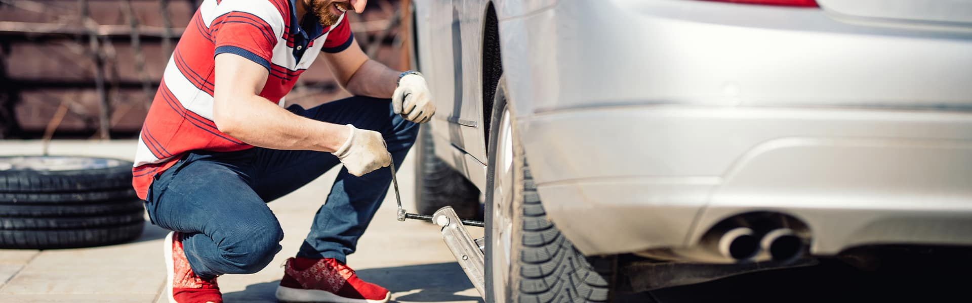 How to change a tire step-by-step guide at Halterman's Toyota in East Stroudsburg | Man using Car Jack on Car in Order to Lift Up and Change Tire on Vehicle