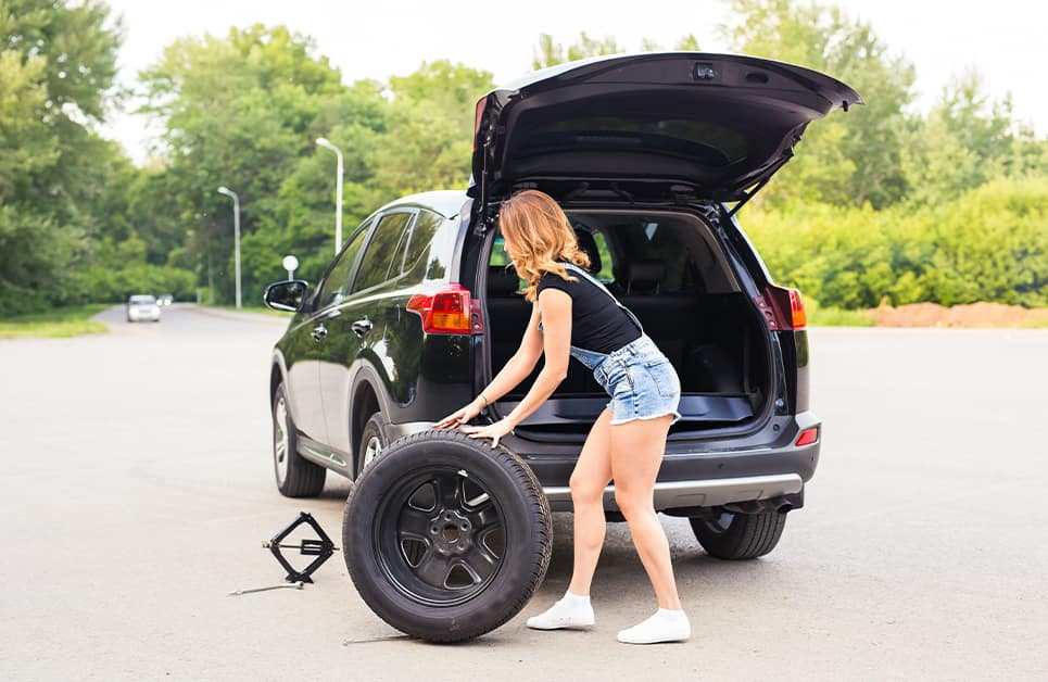 How to change a tire step-by-step guide at Halterman's Toyota in East Stroudsburg | Woman Rolling Spare Tire After Getting it Out of Her Trunk