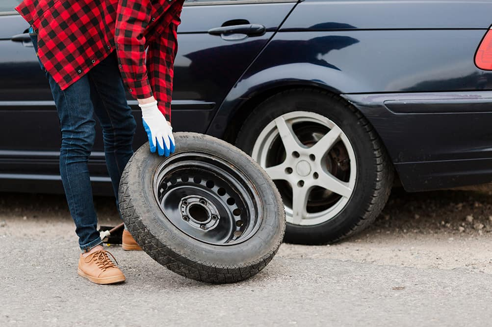 A step-by-step guide to changing a tire by Halterman's Toyota in East Stroudsburg | Man taking spare tire out of trunk