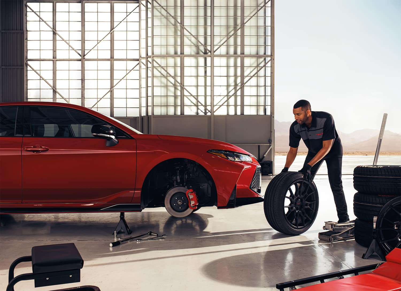 Halterman's Toyota is a Toyota Dealership near Hackettstown, NJ | Toyota mechanic changing tire on Toyota Camry