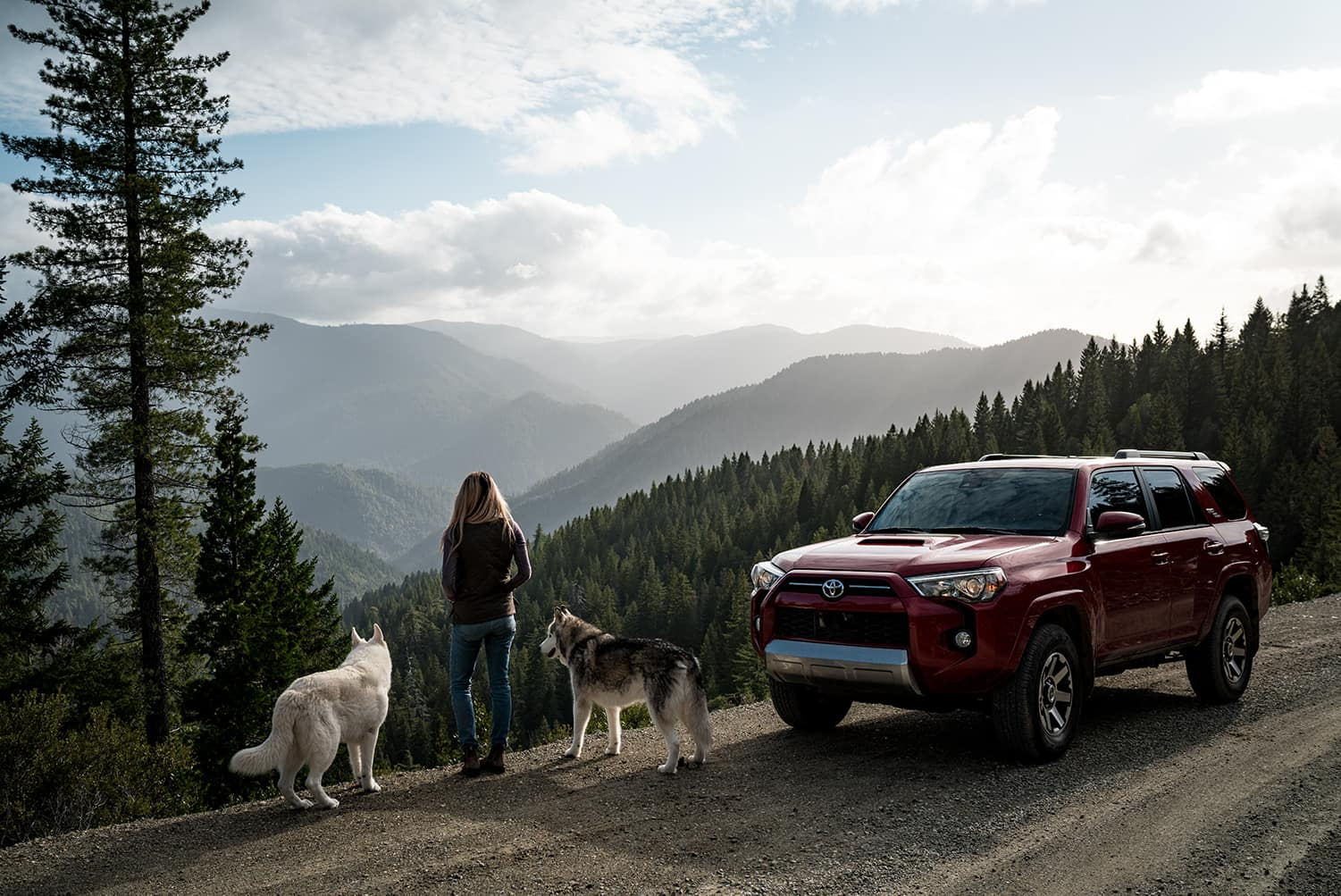 Halterman's Toyota is a Toyota Dealership near Swiftwater, PA | Woman and her two dogs on top of a mountain with their Toyota 4Runner