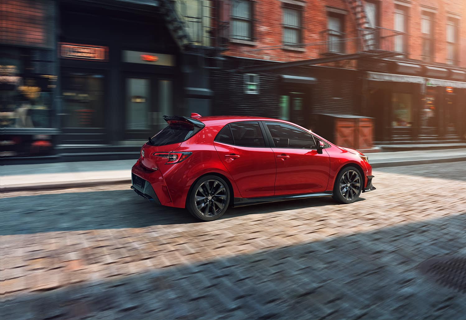 Halterman's Toyota is a Toyota Dealership near Swiftwater, PA | 2021 Toyota Corolla Hatchback driving on brick road