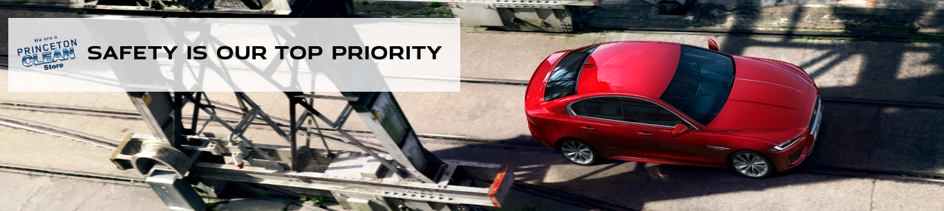 SAFETY IS OUR TOP PRIORITY. RED JAGUAR XE DRIVING DOWN ROAD DOWN BRIDGE.