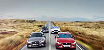 Jaguar vehicles driving down road