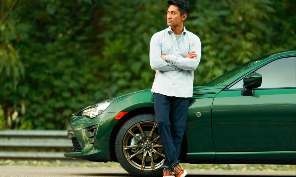 Man leaning against green car parked on the side of the road