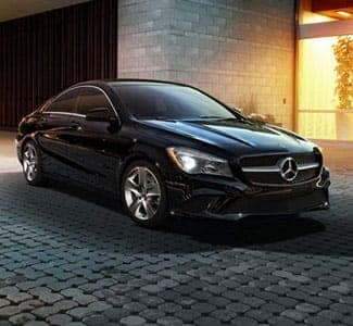 Black Mercedes Sedan Parked by building at night