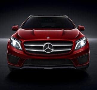Red Mercedes Sedan in dark with headlights on