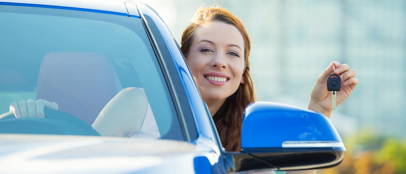 happy woman inside vehicle holding car keys