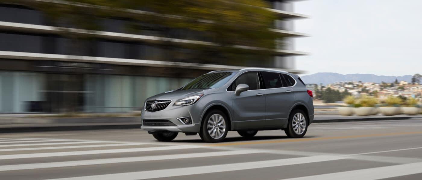 A silver 2020 Buick Envision driving down a road