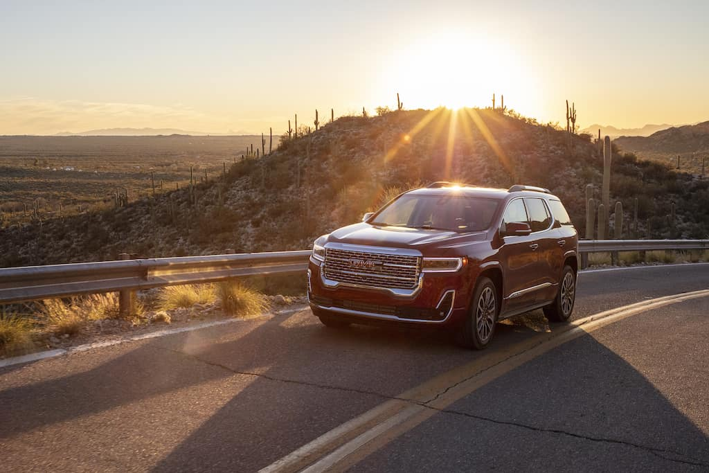 red gmc acadia driving outdoors