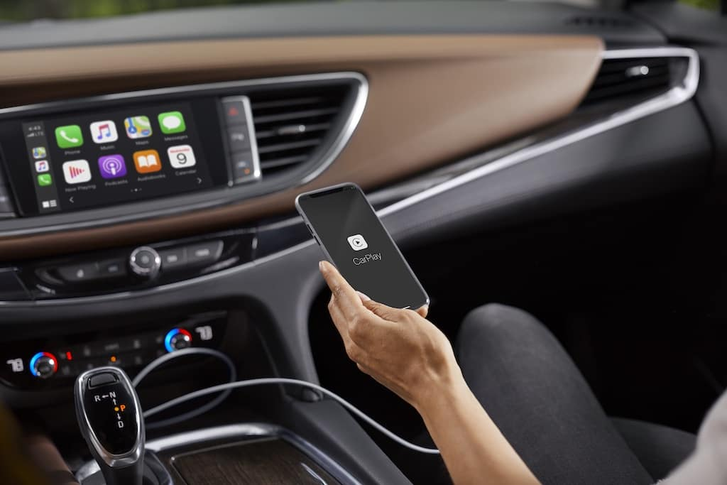 2021 Buick Enclave Avenir (1SP) Chestnut (HHH) interior - view of Apple CarPlay on infotainment screen. Lifestyle, talent, female passenger with smartphone in hand.
