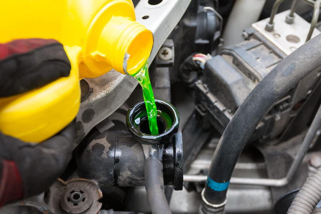 green coolant pouring into engine