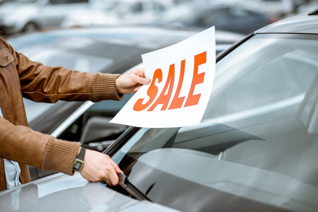 Salesperson putting sale plate on the car