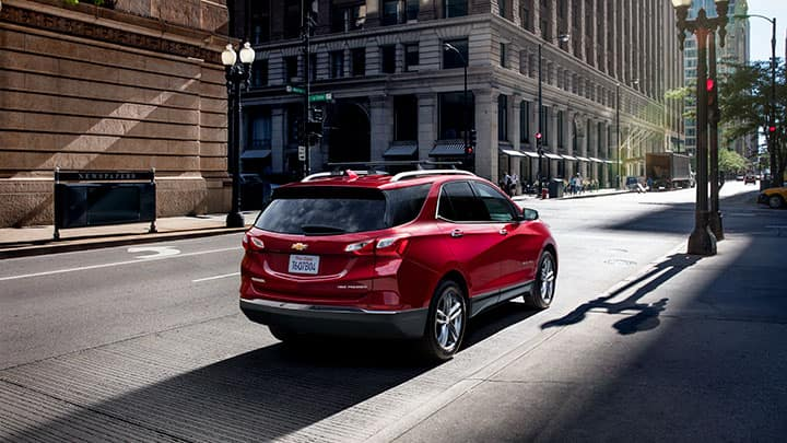 Chevrolet Equinox Premier in Cajun Red Tintcoat parked on a city street; 3/4 passenger side rear.