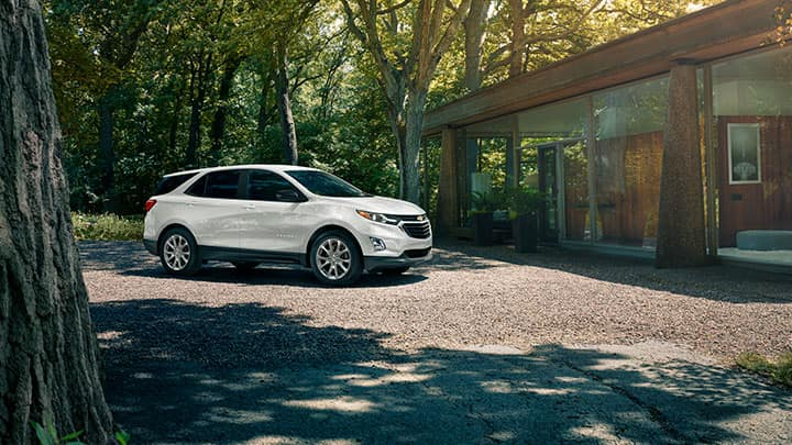 Chevrolet Equinox LS [1LS] in Summit White; 7/8 Passenger side front view in front of a modern home; trees, sun, shade