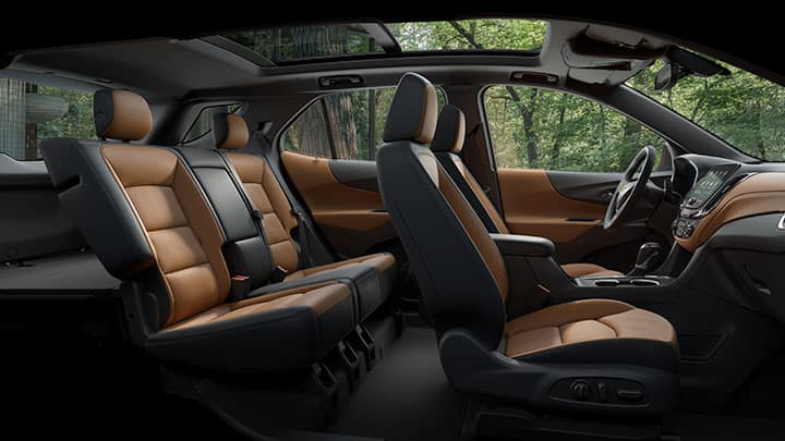 Chevrolet Equinox Premier interior shot: Chevy infotainment system 3 on 8 inch diagonal screen, Brandy with Jet black accents leather appointed interior, Panoramic sunroof (open), and 3 spoke leather wrapped steering wheel.