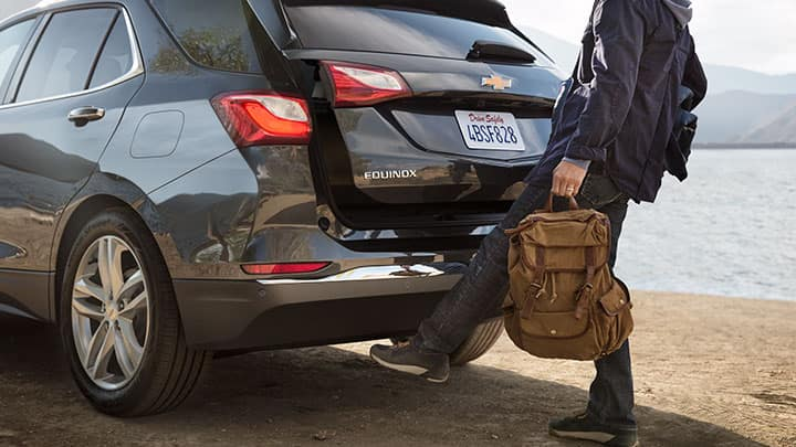 Chevrolet Equinox Premier [1LZ] in Graphite Metallic, 3/4 drivers side rear view with talent using hands-free power liftgate. Beach; water.