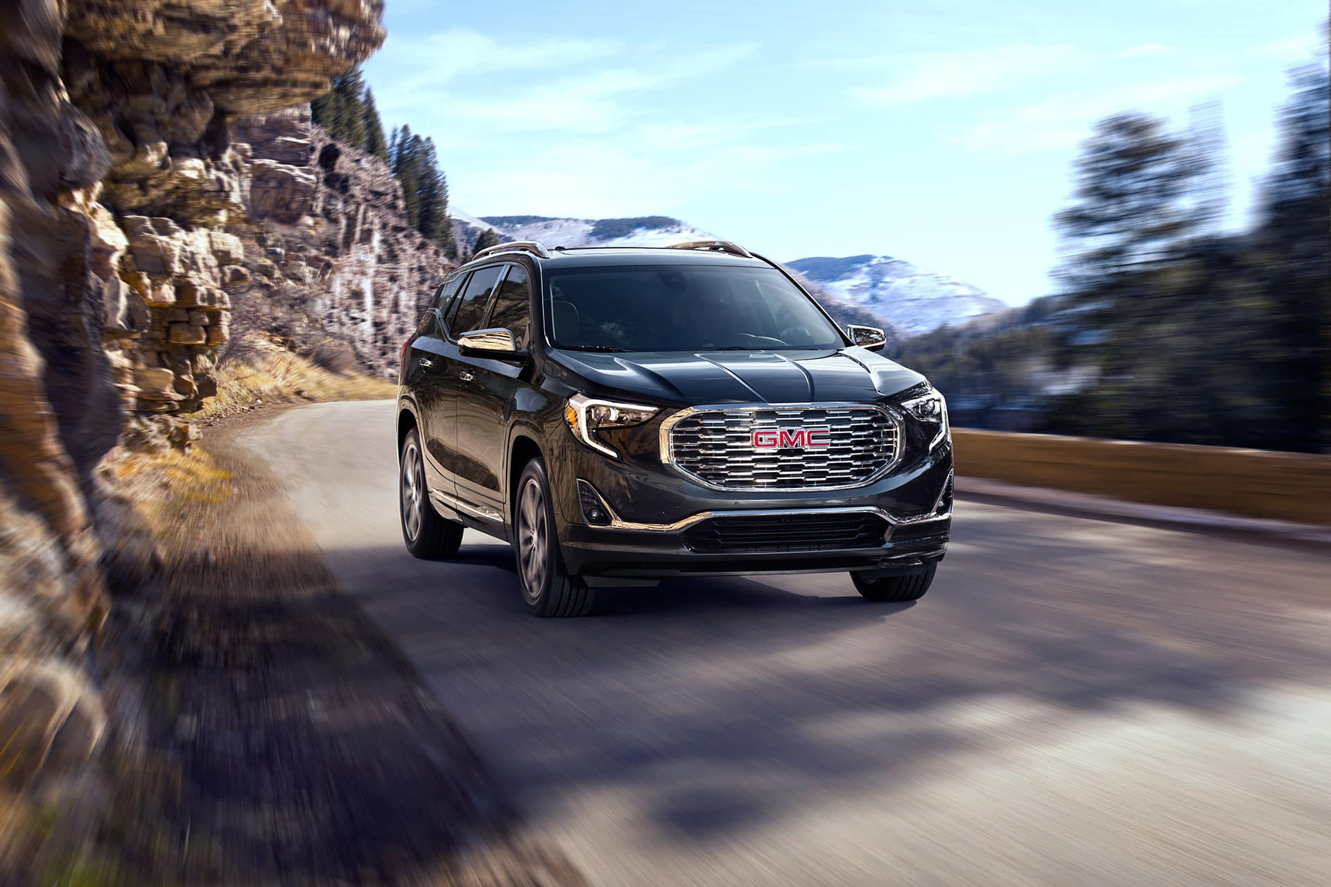 "2021 GMC Terrain Denali Exterior in Graphite Gray Metallic with (RT7) 19"" Ultra-Bright Machined Aluminum Wheels; 3/4 Passengers side Front; Road shot/motion; Mountains in background; Vail, Colorado Location."