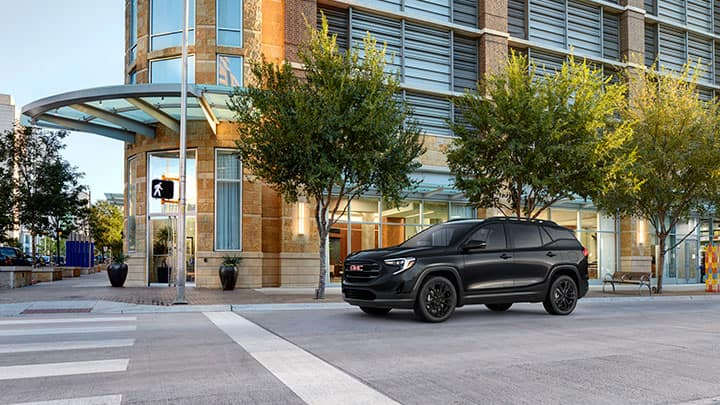 "2021 GMC Terrain SLT Black Edition Exterior in Ebony Twilight Metallic; 7/8 Drivers side Front; Black Edition Includes 19"" Gloss Black Aluminum Wheels, Darkened Grille / Grill Insert and Black Surround, Black Mirror Caps, Roof Rails, and Black Exterior Model and Trim Badging; On urban / city street"