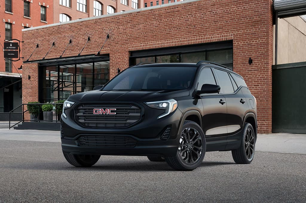 "2021 GMC Terrain SLE Elevation Edition Exterior in Ebony Twilight Metallic with (PJM) 19"" Gloss Black Aluminum Wheels; 3/4 Drivers side Front; Parked in front of urban / industrial brick building"