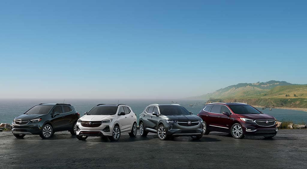 2021 Buick 4 SUV pack shot. Left to right includes: 2021 Encore Preferred (1SB) shown in Ebony Twilight Metallic with RRU wheels. 2021 Encore GX Essence (1SL) shown in White Frost Tricoat with RQJ wheels. 2021 Envision Avenir (1SU) shown in Satin Steel Metallic with RTJ wheels.. 2021 Enclave Avenir (1SP) shown in Rich Garnet Metallic with SME wheels. City background