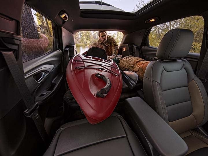 2021 Chevrolet Trailblazer ACTIV interior view of man loading Kayak into rear of vehicle demonstrating vehicle cargo management.