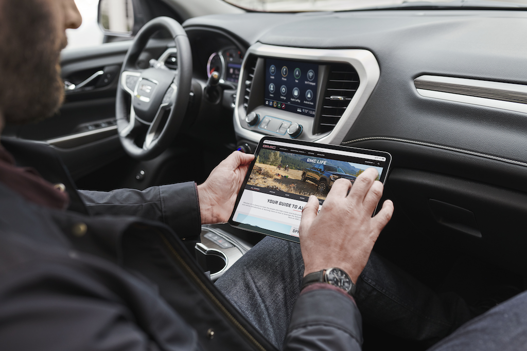 2021 GMC Acadia SLT 4G LTE WiFi Scenario; Lifestyle with talent in passengers seat with tablet on GMC.com
