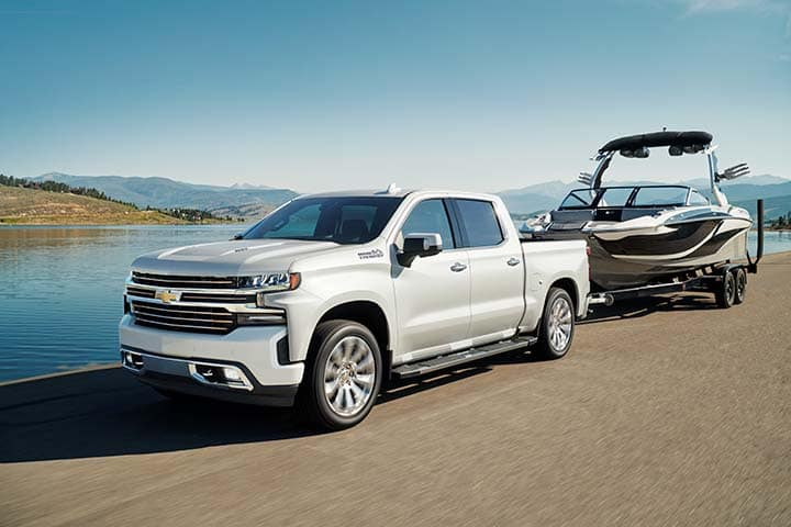 Chevy Silverado 1500 Crew Cab High Country [3LZ] 4x4 shown in Iridescent Peral Tricoat towing a boat.