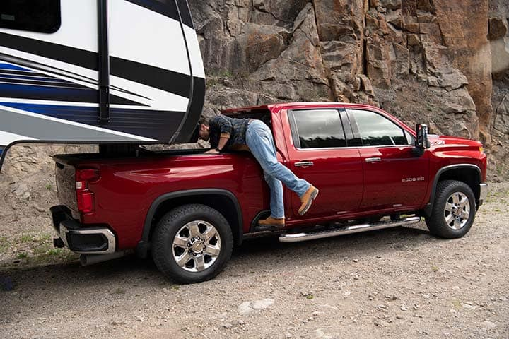 2021 Chevy Silverado 1500 in red towing an RV trailing, man looking into bed of truck.