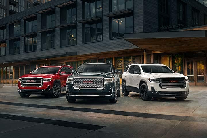 2021 GMC Acadia Family/Pack Shot Featuring (L to R) - Acadia SLT AWD in Cayenne Red Tintcoat; Acadia Denali AWD in Hunter Metallic; Acadia AT4 AWD in Summit White; Urban Location