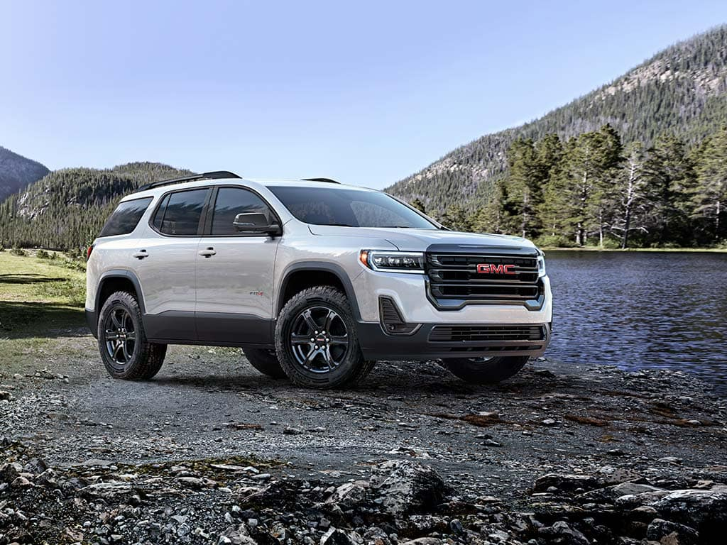 """2021 GMC Acadia AT4 AWD Exterior in Summit White with (Q7D) 17"""" Machined Aluminum Wheels; 3/4 Passengers side Front; Exterior; Mountains and lake in background"""
