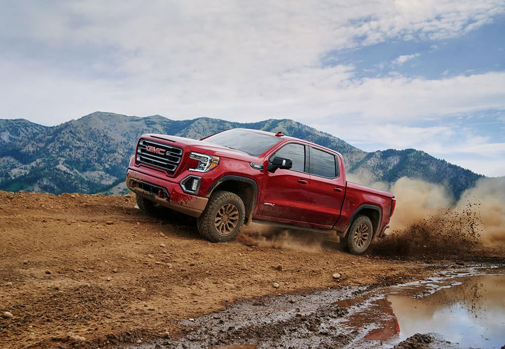 """2021 GMC Sierra 1500 AT4 Crew Cab Short Box 4WD in Red Quartz Tintcoat with (RT5) 18"""" Machined Aluminum Wheels and Available (LM2) Duramax 3.0L Turbo-Diesel I6 Engine; with High Clear Step; 7/8 Drivers side Front; Driving through mud with mountains in background"""