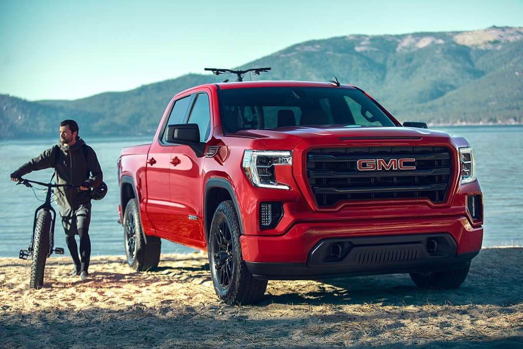 """2021 GMC Sierra 1500 Elevation Crew Cab Short Box in Cardinal Red with (RD3) 20"""" Black Gloss Painted Aluminum Wheels; 3/4 Passengers side Front; Lifestyle with Talent; Mountain bike/bicycle props; Waterfront location with mountains in background"""