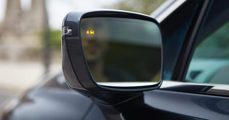 2021 Buick Enclave Avenir (1SP) in Dark Slate Metallic - close up of driver side view mirror. Highlights Active Safety Detection Family, with Lane Change Alert with Side Blind Zone Alert.